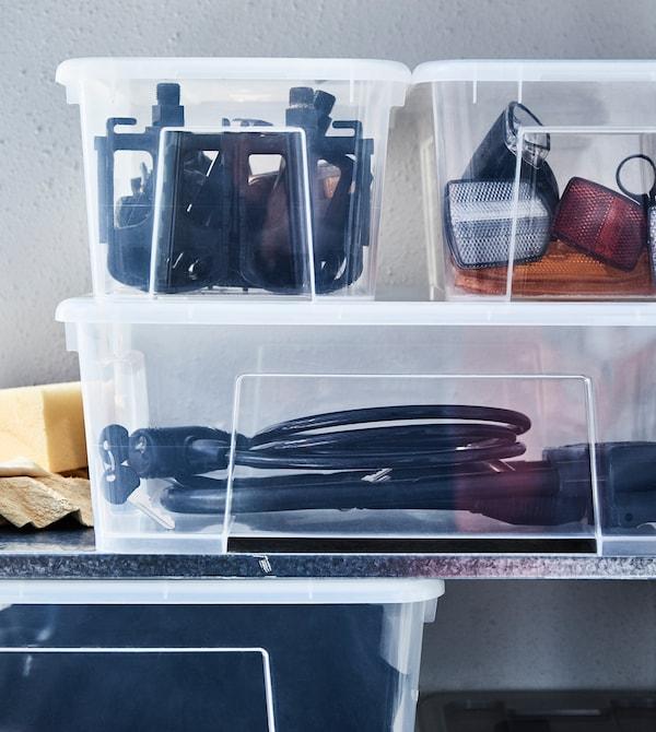 户外用具和运动配件存放在搁板上的透明塑料盒里。