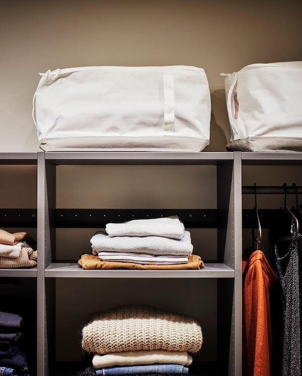 灰色开放式衣柜顶层放着两个带提手的白色/米色储物袋,为换季衣物提供储存空间。