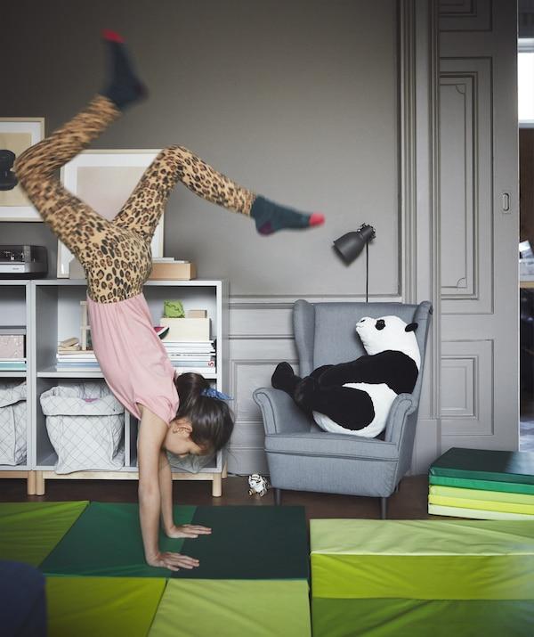 灰色客厅里摆放着亮绿色的儿童游戏垫,一个女孩在倒立。