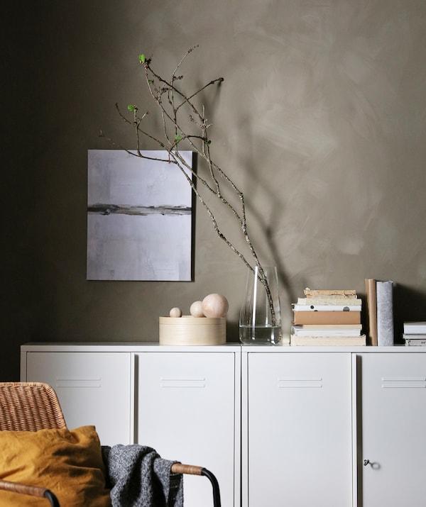 灰色墙边靠着一排灰色储物柜。柜子上放着书籍、装饰品和插着发芽嫩枝的花瓶。