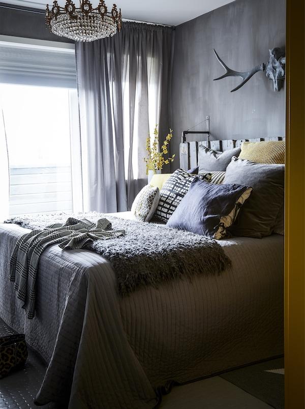 灰色卧室搭配黄花和靠垫。