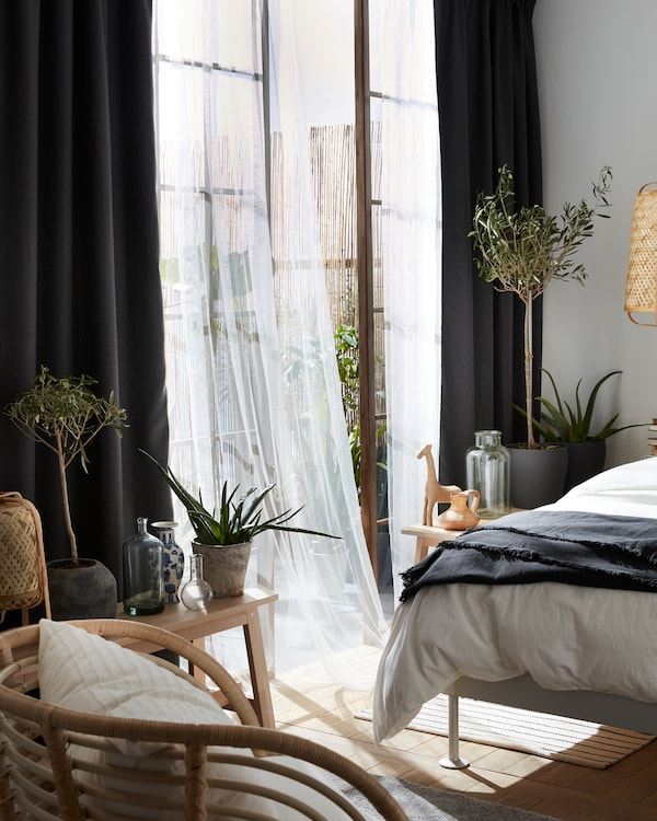灰色遮光窗帘搭配白色透明窗帘、BUSKBO 布克伯 扶手椅和盆栽橄榄树。