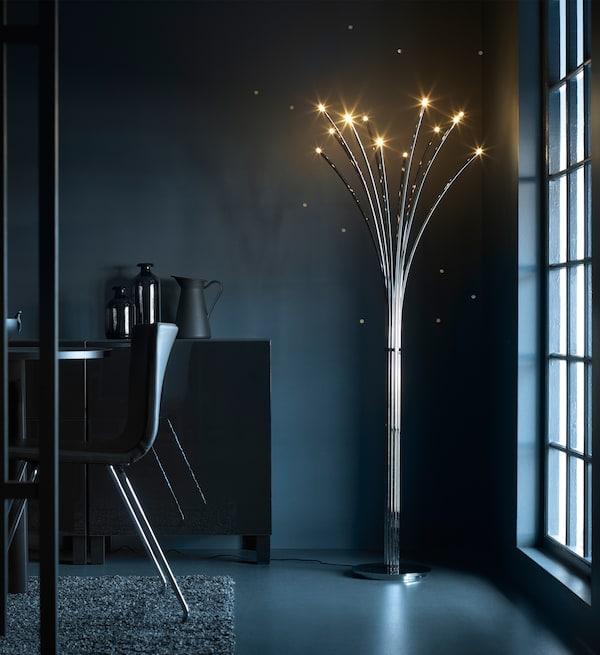 昏暗餐厅的角落里摆放着一盏点亮的落地灯。落地灯的底座为不锈钢材质,顶部为闪闪发光的LED灯,看起来就像萤火虫一般。