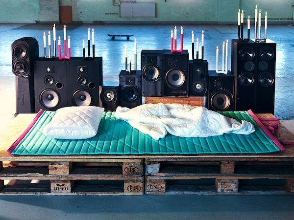 货盘上展示着浅绿色的夹棉地垫,上面放着白色夹棉休闲毯和靠垫。背景中,银色、粉红色、深蓝色和白色烛台放在大型扬声器的顶部。
