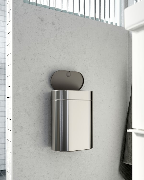 IKEA BROGRUND touch top bin in stainless steel that is mounted on a wall right next to the wash basin.