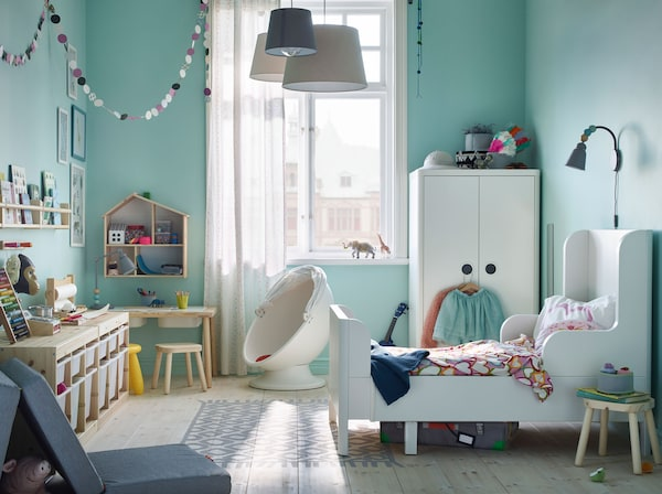 IKEA BUSUNGE white extendable bed and wardrobe along with FLISAT light wood children's table can transform a room into a playground with safe moving parts.