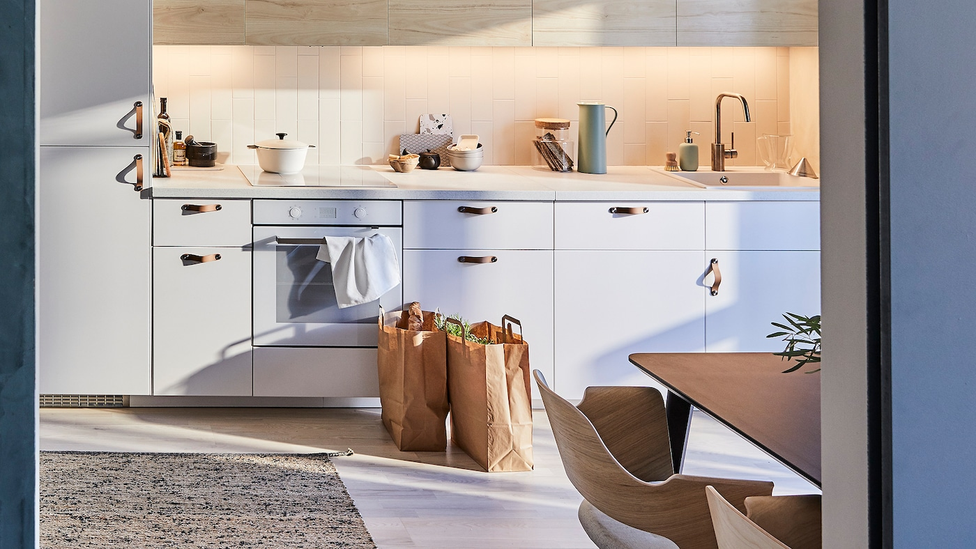 IKEA METOD kitchen with light wooden ash-effect door fronts and a flatwoven rug made from jute and wool.