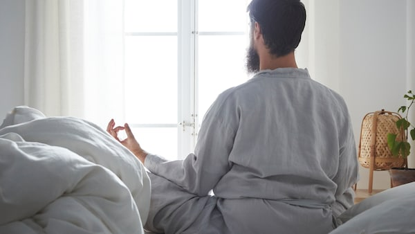 In a calm-looking bedroom, a bearded man sits cross-legged on a bed in a meditation pose, looking out the window.