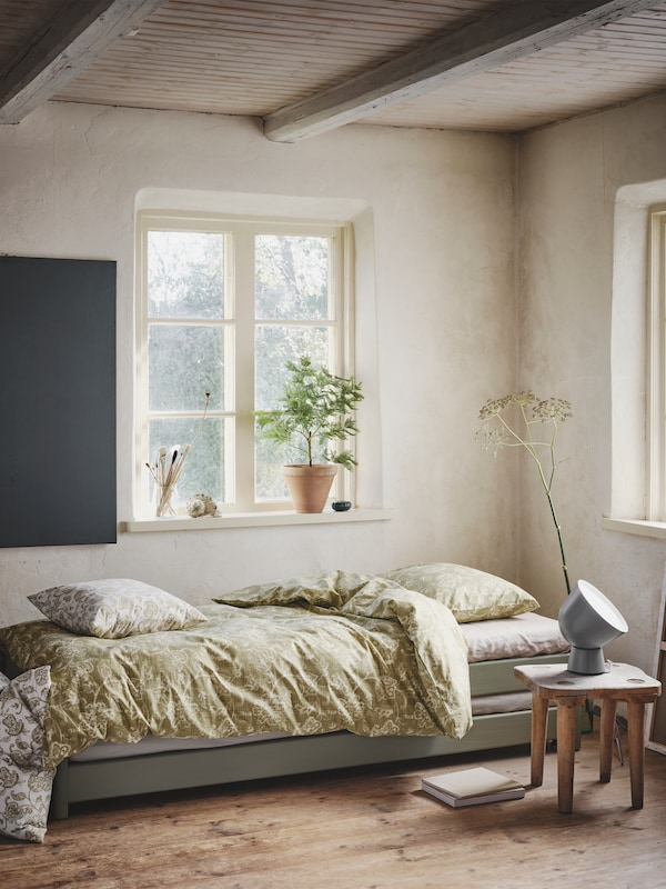 In the corner of a well-lit room with wooden ceilings stands a cosy daybed with an olive green JUNIMAGNOLIA bedding set.