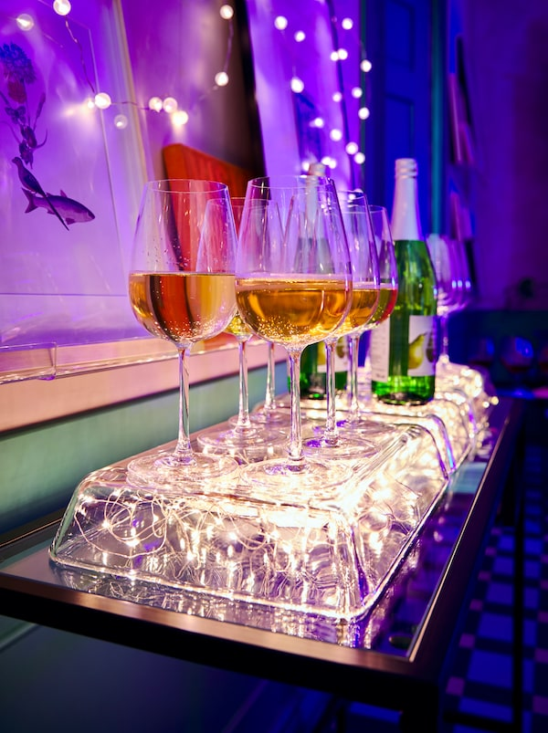 Inverted MIXTUR glass oven dishes with VISSVASS lighting chains underneath, forming a glowing stand for filled wine glasses.