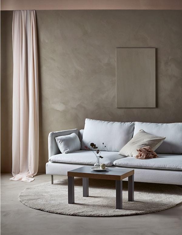 简约风格的客厅里面摆放着一张沙发和沙发桌,墙壁上挂着单件艺术品。
