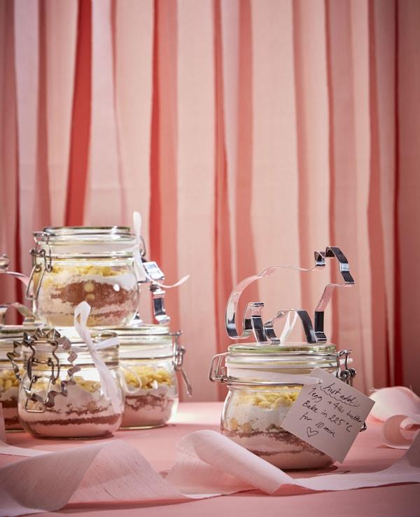 将饼干制作原料铺在玻璃罐中,并附上手写的留言和饼干模具。