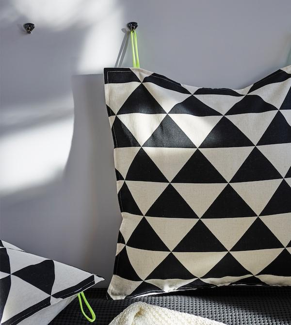 将两个带有黑白不规则印花的靠垫挂在墙上,把床变成舒适的坐卧两用床。
