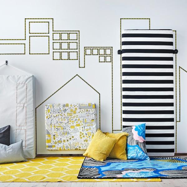 """将套有纺织品垫套的床垫紧紧固定在墙上,再用上装饰胶带,即可打造出一道""""城市天际线""""。"""