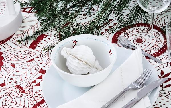 节日餐桌布置的一角。带图案的桌布,LED蜡烛,云杉树枝,纸制装饰品。
