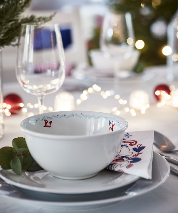 节日餐桌布置中的单人部分。多个碟子,桌子上装饰着灯串装,还有冬青枝装饰和酒杯。