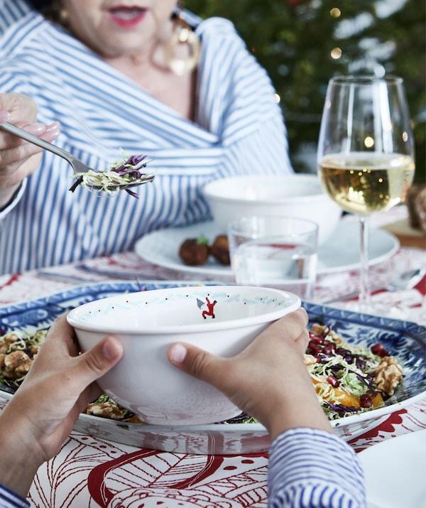 节日餐桌的一角,包含盛有美酒佳肴的碟子和杯子。一位长者在给孩子手中的碗添食物。