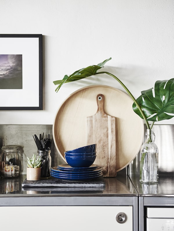 金属操作台面上摆放着厨具和植物。