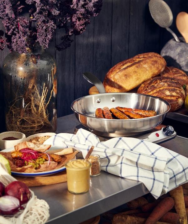 金属操作台面上摆放着一盘食物,称重台上放着几条面包和香肠。