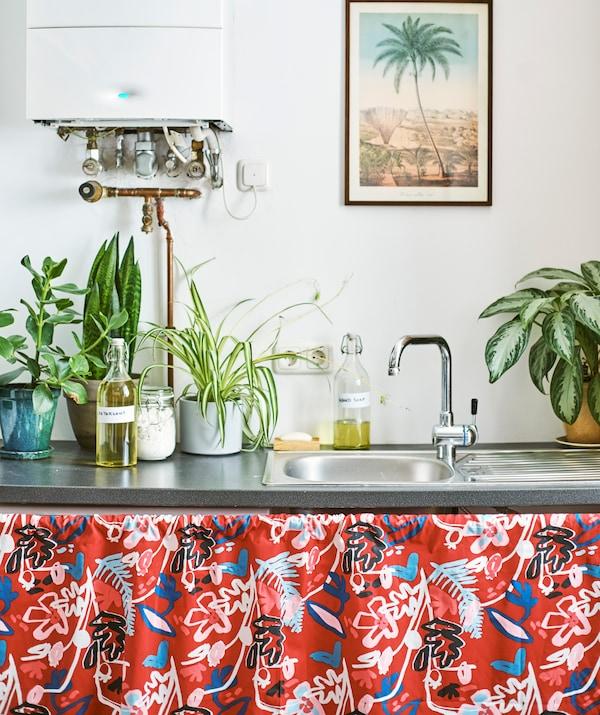 金属水槽上放着植物和装满液体的瓶子。水槽下面铺着带红色图案的布料。