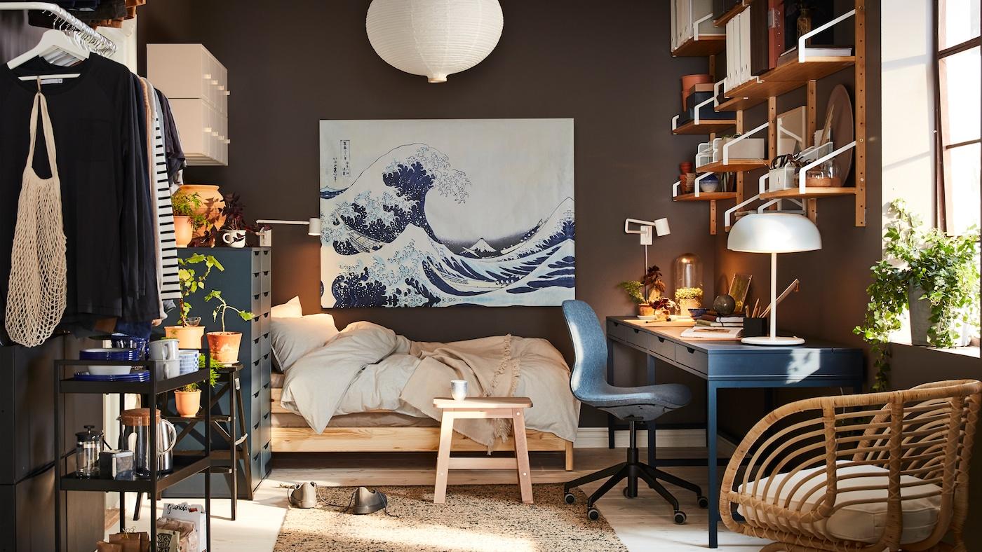 紧凑的家里,有一张深蓝色书桌、一张藤制扶手椅、一盏白色吊灯和一幅蓝色波浪图画。