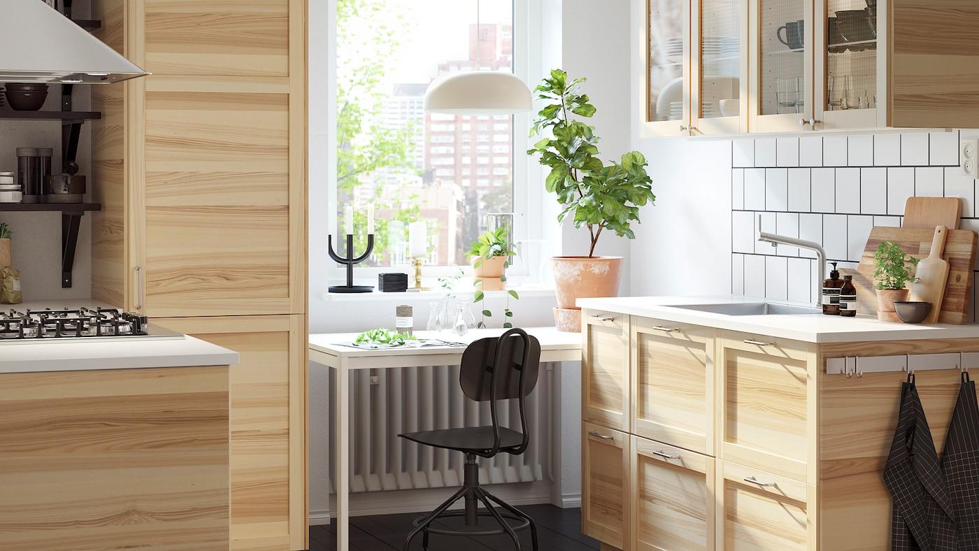 紧凑却明亮的厨房,原色白蜡木和玻璃橱柜打造传统风格,窗前放着一张白色桌子。