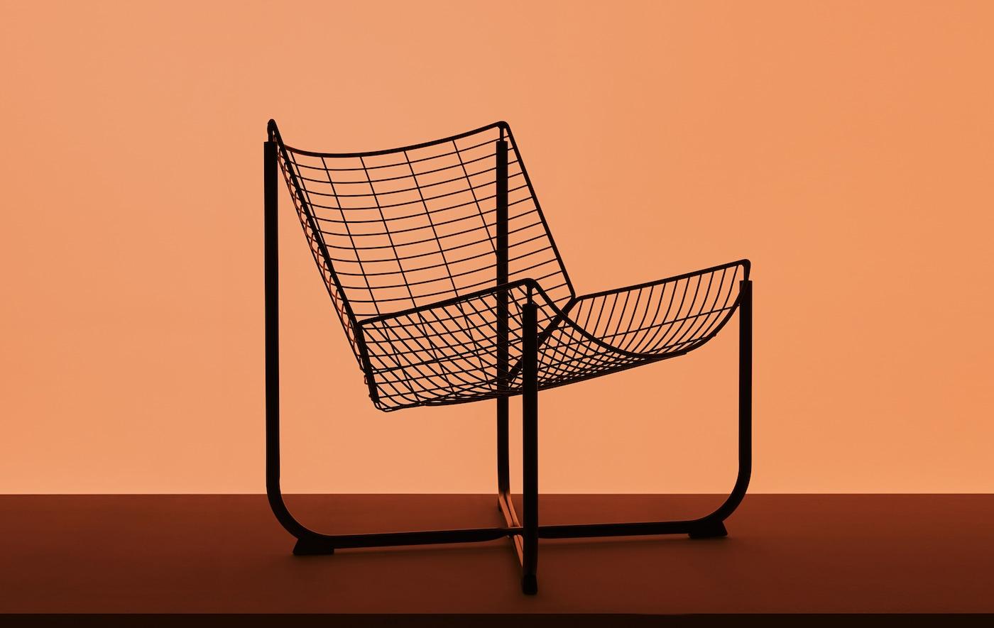 橘色背景前,摆放着一张黑色网格扶手椅。