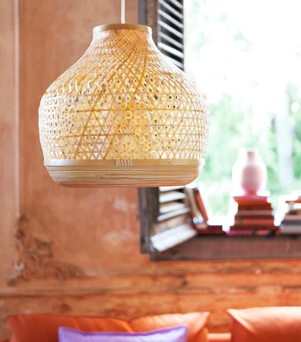 橘色的墙壁前悬挂着编织吊灯,背后有深色的木百叶窗和几本书。