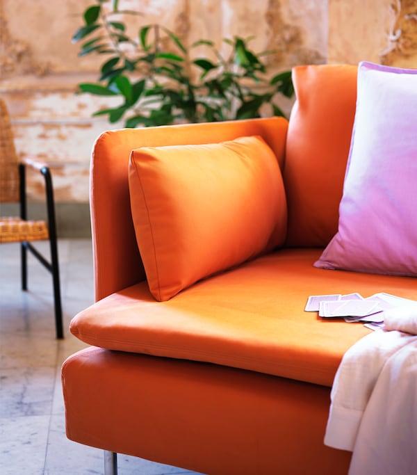 橘色沙发上摆放着粉色枕头和浅粉色休闲毯。沙发上散落着一些卡片。