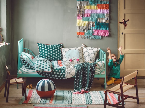 KÄPPHÄST quilt cover, rug and cushions in a colourful room with a child throwing a toy monkey up in the air.