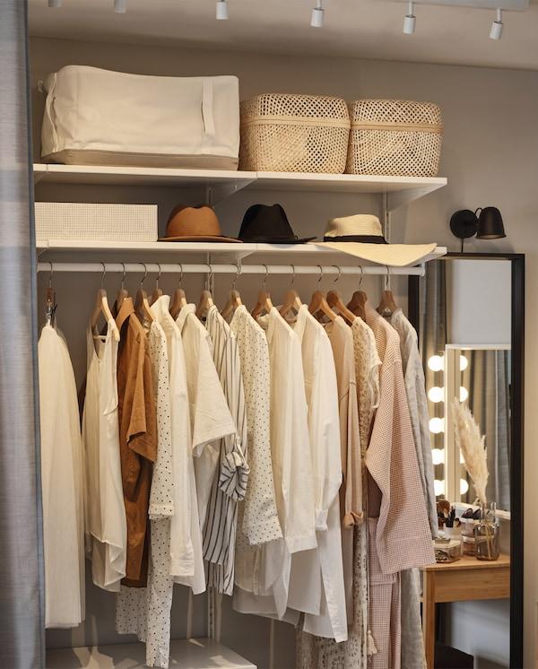 开放式储物系列的挂衣杆上挂着衣服。上方的搁板上放着储物袋、储物盒和帽子。