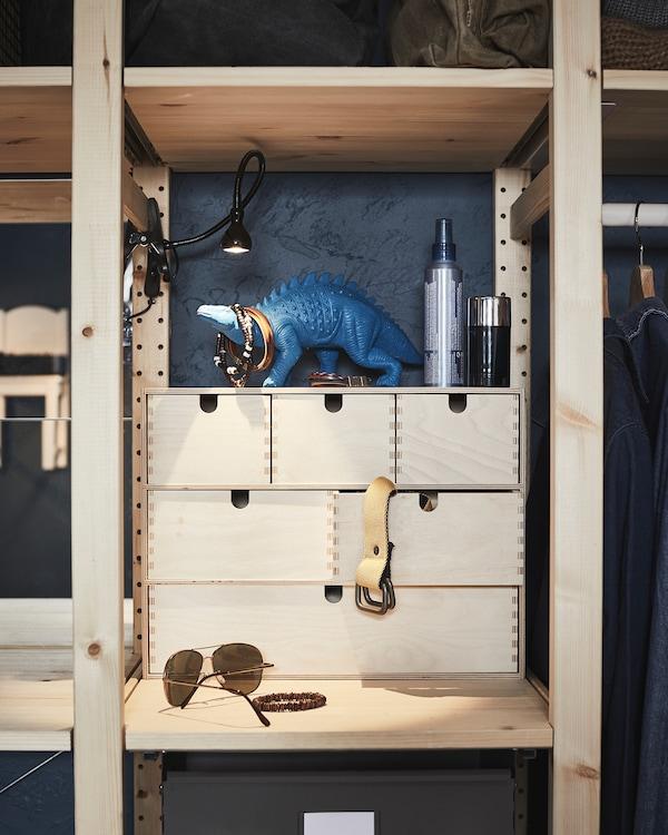 开放式木材搁架单元的搁板上放着小型抽屉柜,柜子里和柜子周围摆满青少年常用的杂物配件。