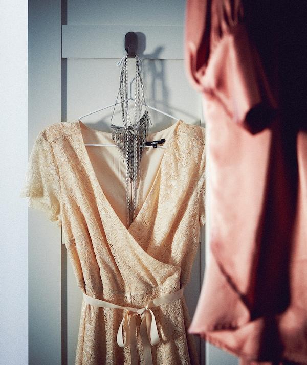 开放式衣柜的柜门上配有挂钩,上面挂着一个衣架,衣架上是一件无领无袖晚礼服裙。