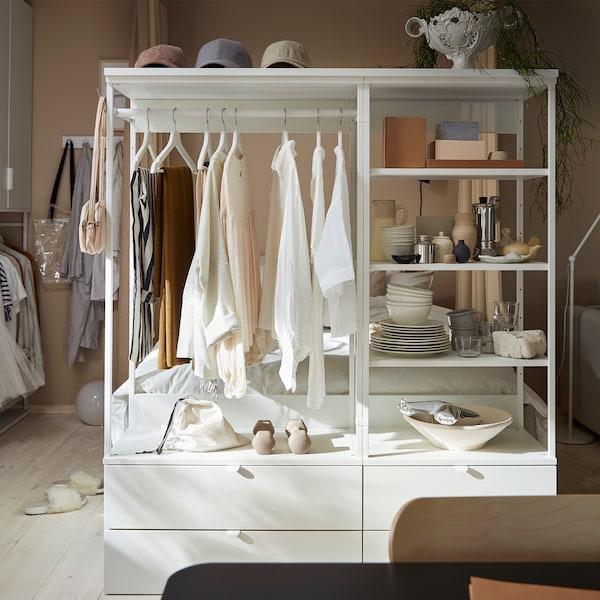 开放式衣柜配有抽屉、搁板和挂杆。衣服悬挂在白色衣架上,装饰品置于搁板上。