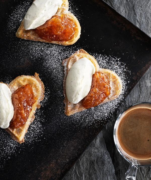 烤盘上放着三个涂抹着果酱和鲜奶油的心形华夫饼,旁边的玻璃杯中盛着咖啡。