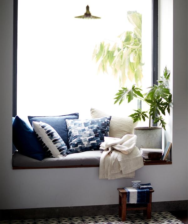靠窗的座位上摆放着靠垫和植物。