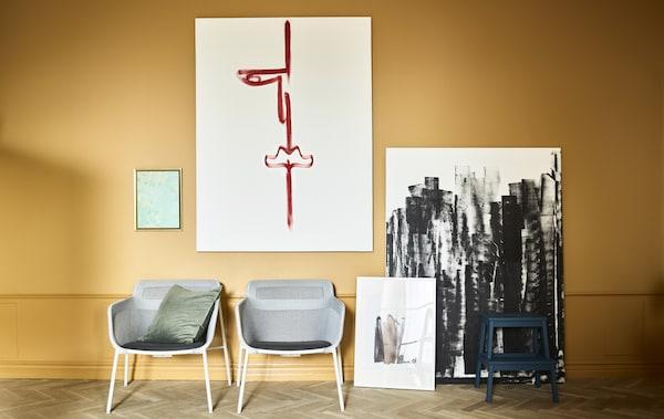 靠在赭色墙壁上的两把扶手椅和自制艺术品。