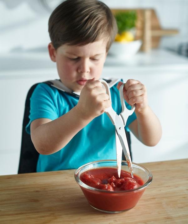 可以用剪刀来轻松地切割蔬菜,让孩子操作也很安全,就像这样:用来搅碎碗里的西红柿。