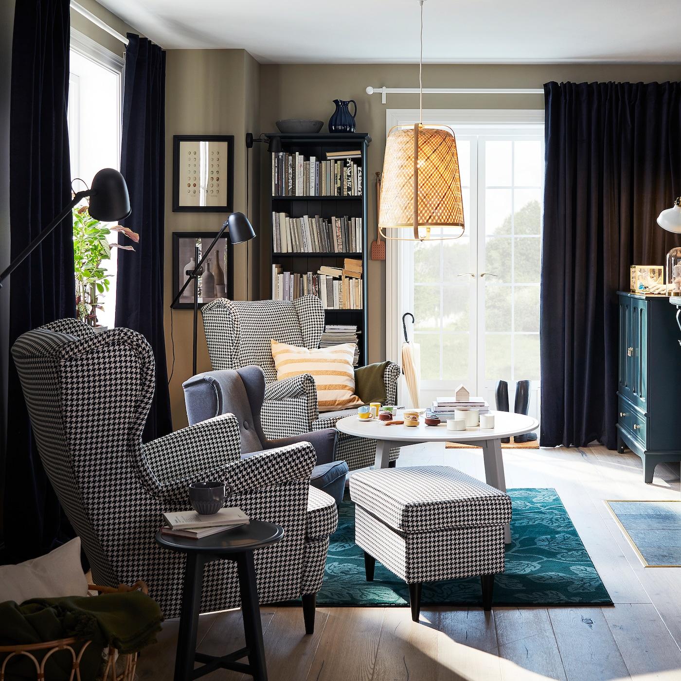 客厅摆放着两张犬牙图案靠背椅、绿色地毯、竹质吊灯和圆茶几。