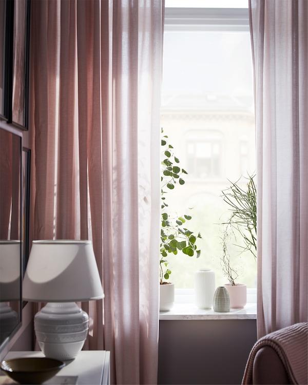 客厅窗户配有过滤光线的 HANNALILL 汉娜利尔 粉色挂帘,窗台上摆放着一些植物和花盆。