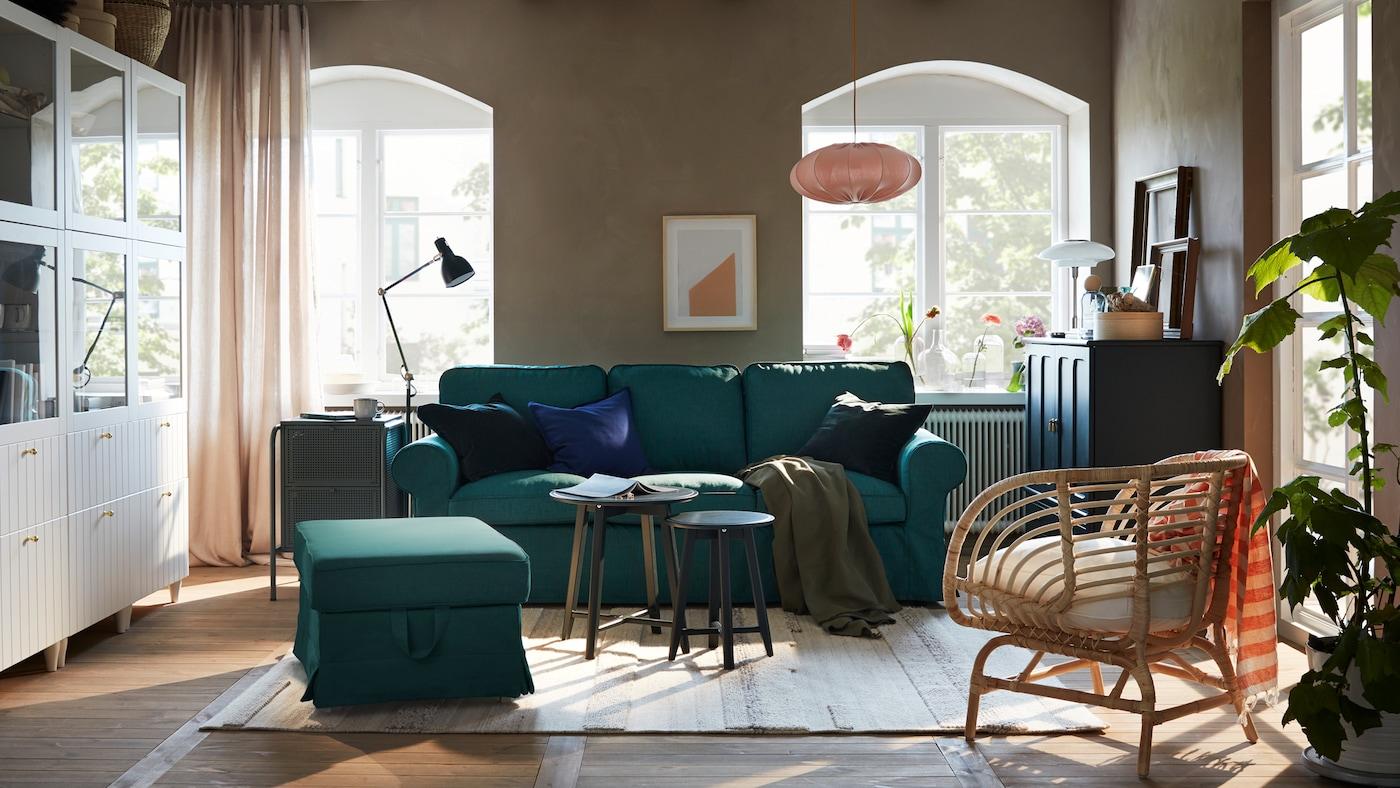 客厅里摆放着深青绿色的沙发和脚凳、白色的储物组合和深青绿色的储物柜。