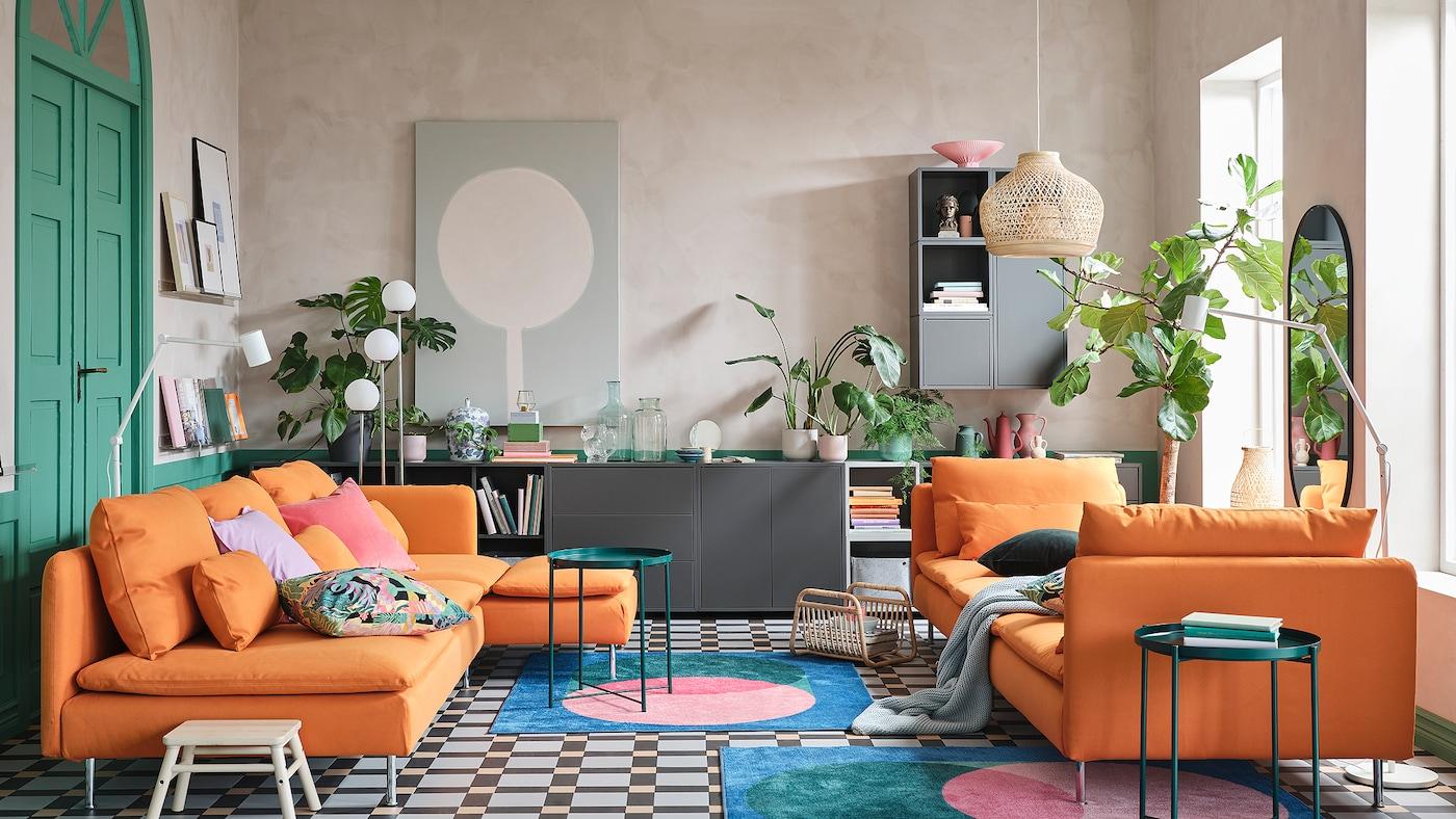 客厅里放着橙色沙发和贵妃椅、灰色的储物柜组合、彩色的地毯和绿色的托盘式桌子。
