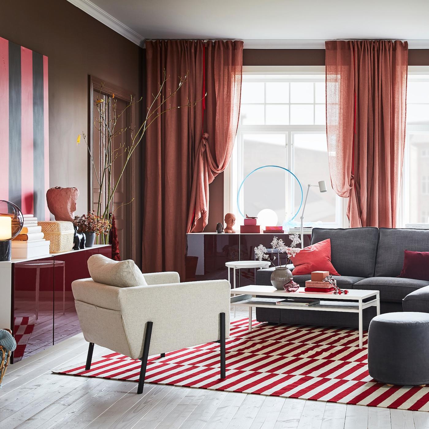 客厅里挂着棕粉色窗帘,摆放着红色/白色地毯、灰色沙发和红色高光柜门壁装储物柜。
