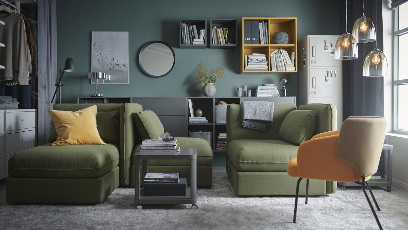 客厅里有几张绿色的VALLENTUNA 瓦伦图 模块沙发床、灰色的大地毯、灰色和黄色的柜子,以及玻璃吊灯。