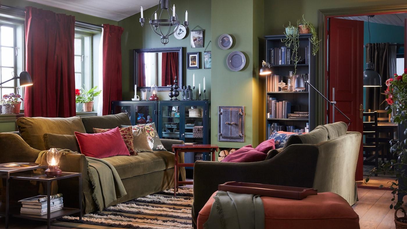 客厅里有两张橄榄绿色的沙发、一张浅红色脚凳、一盏黑色枝形吊灯、红褐色的窗帘和条纹地毯。