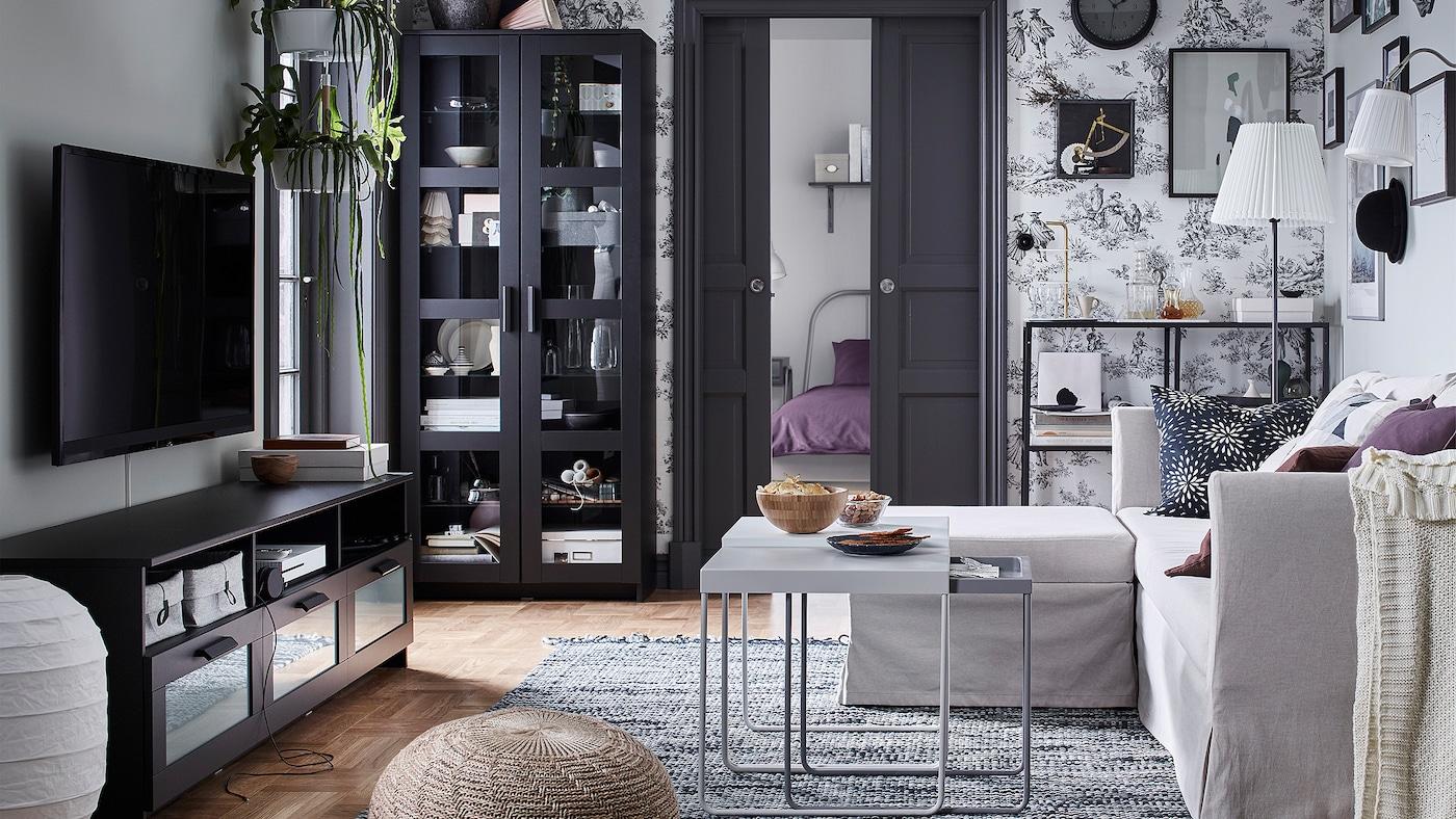 客厅里有一个宜家BRIMNES 百灵 黑色电视柜和带搁架的储物柜,对面是一张SANDBACKEN 桑德巴肯 米色沙发。
