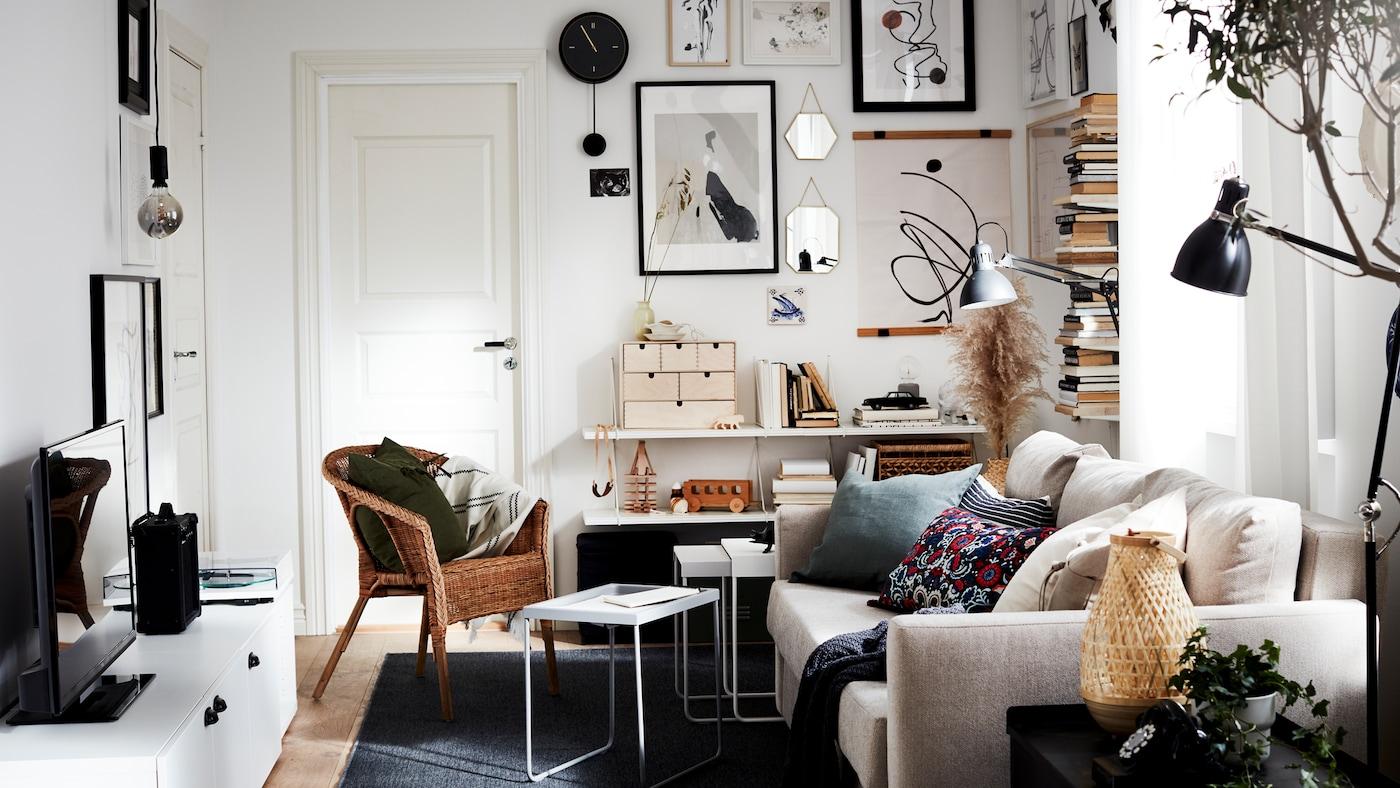 客厅里有一张沙发床、一把藤条/竹制椅子、一张电视柜、一张深灰色地毯、一个黑色挂钟和黑色的灯具。