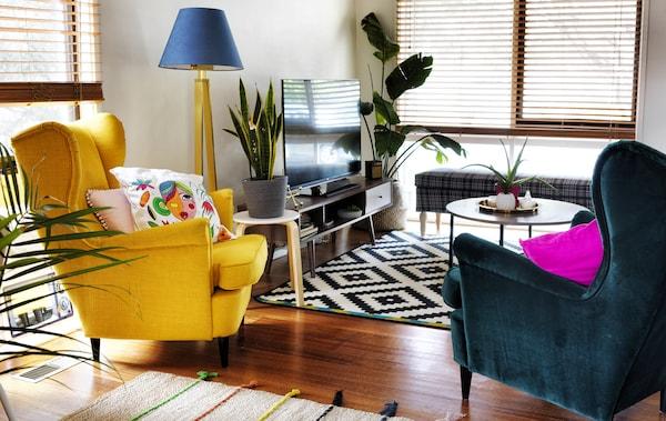 客厅内摆放着两把翼形扶手椅,一把黄色,一把深绿色,还有一块黑白地毯和一台电视。