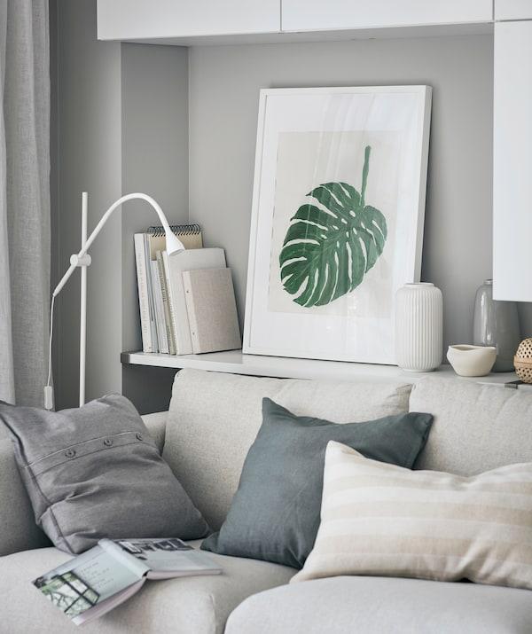 客厅一角摆放着一张沙发,沙发后的墙搁架上放着书籍、装饰品和带框的龟背竹画作。