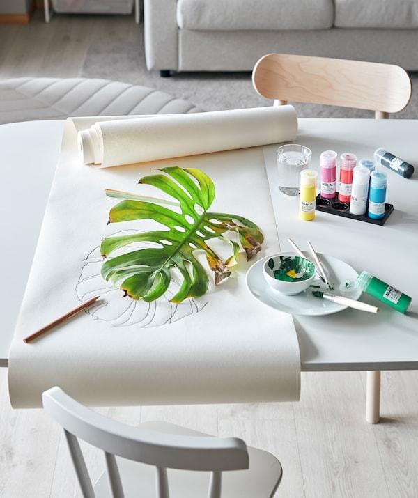 客厅桌子为植物写生活动做好了布置:MÅLA 莫拉 颜料、画纸和部分枯萎的龟背竹叶子。